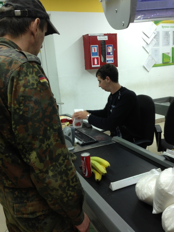 Sitting while is common for checkers at the supermarkets of Ukraine - and yes, this guy was buying 4 giant bags of sugar.